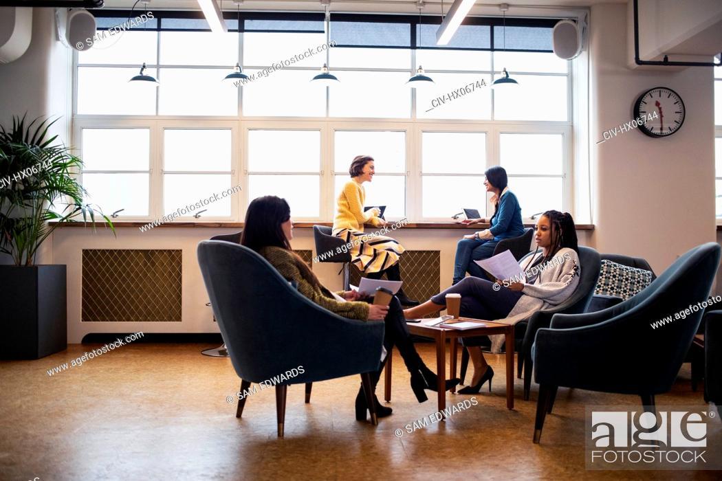 Stock Photo: Businesswomen talking in open plan office.