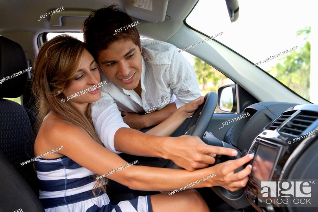 Stock Photo: A man leaning in car window helping his girlfriend with the GPS.