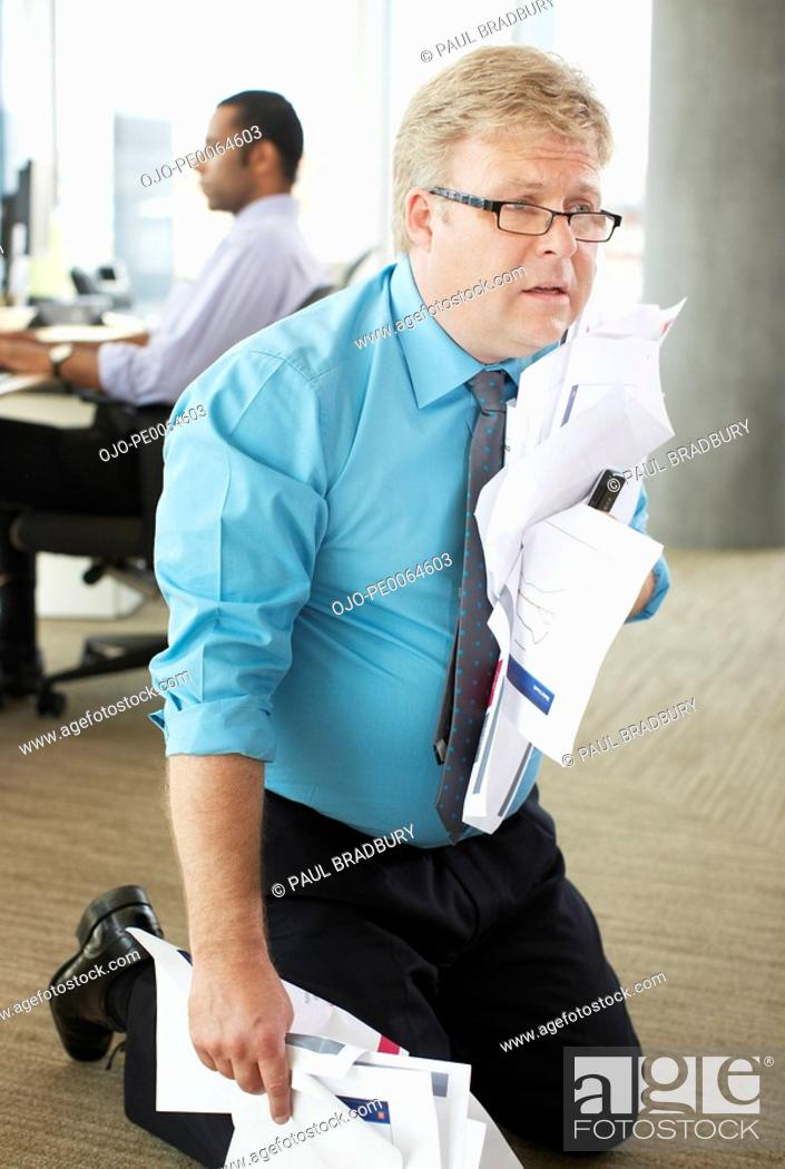 Stock Photo: Frustrated businessman holding crumpled papers.