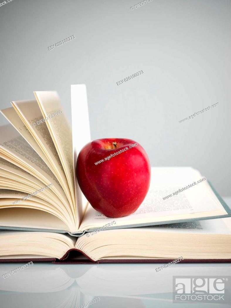 Imagen: red apple on books.