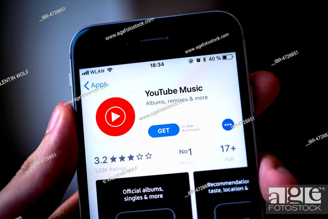 Hand holding iPhone with YouTube Music App in the Apple App