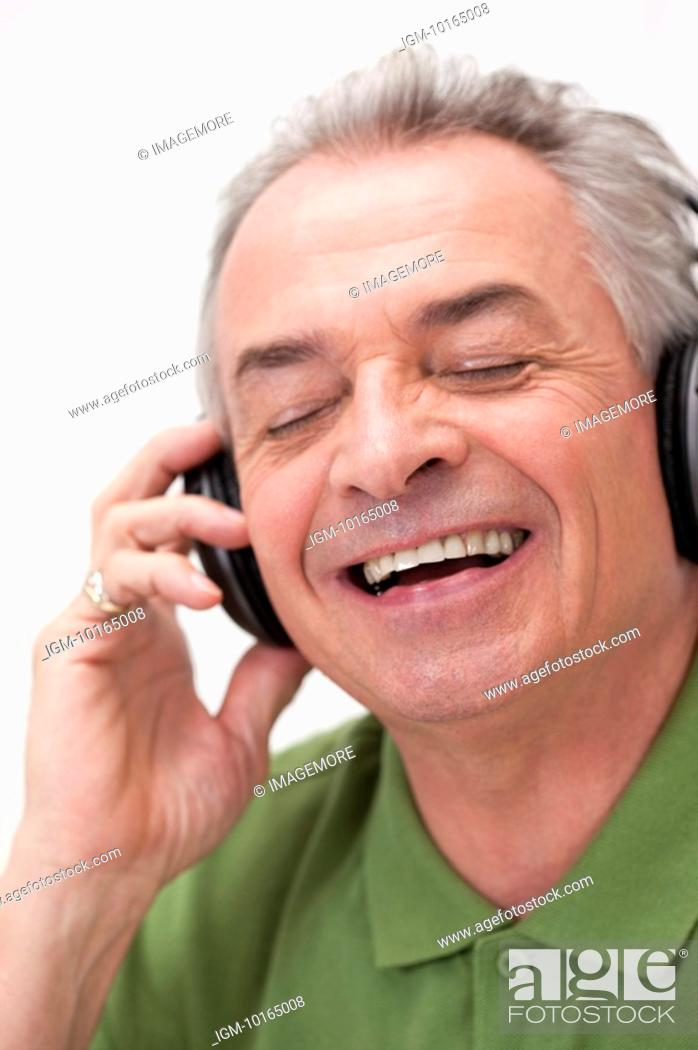 Stock Photo: Senior-aged man listening to music with eyes closed and laughing.