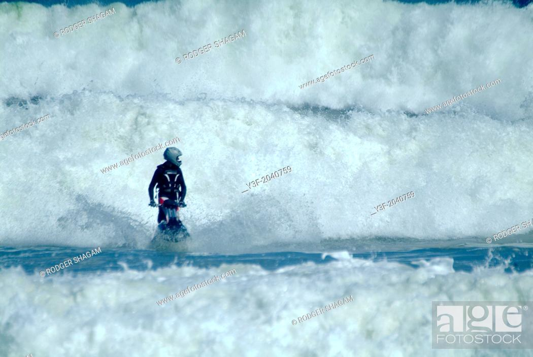 Stock Photo: A man on a jet ski surfs big waves. Cape Town, South Africa.
