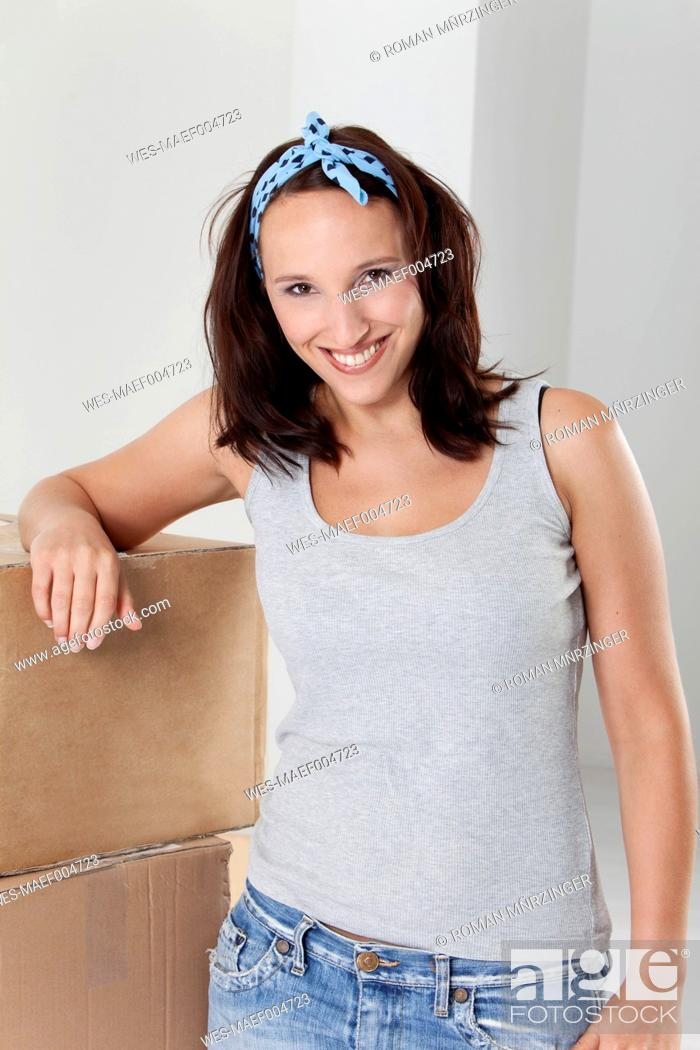 Stock Photo: Young woman leaning at cardboard box, smiling, portrait.