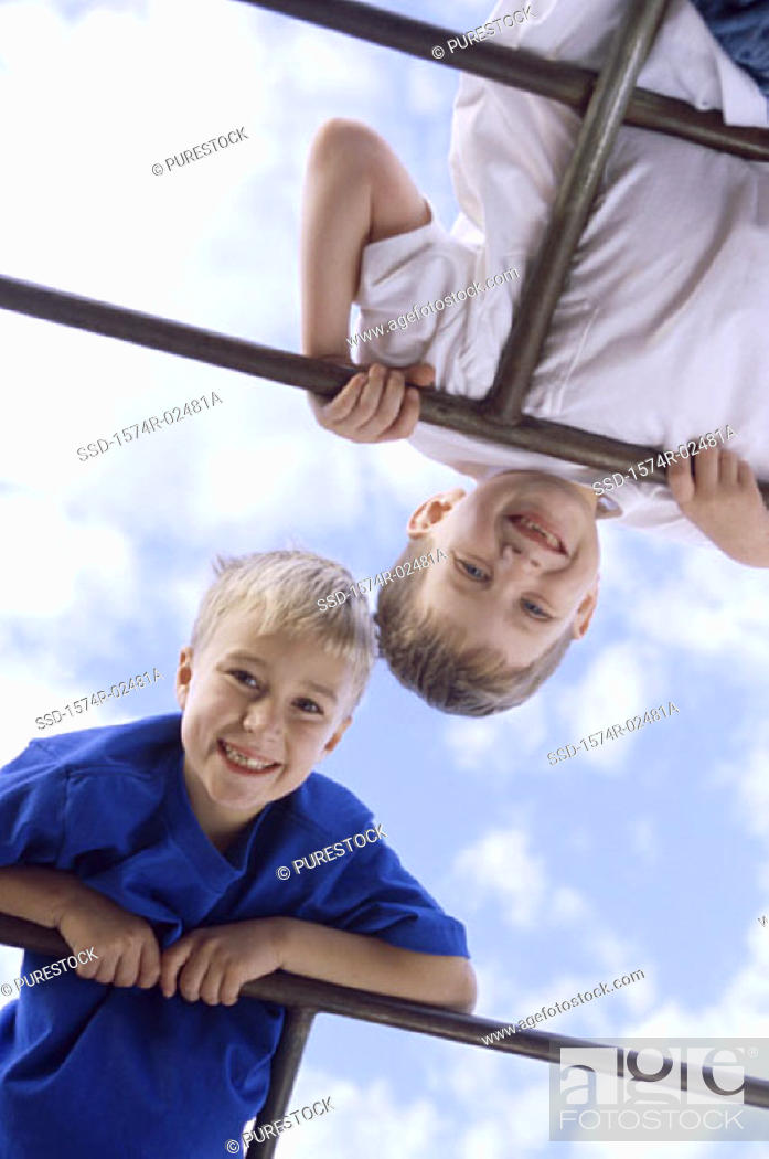 Stock Photo: Low angle view of two boys playing on monkey bars.
