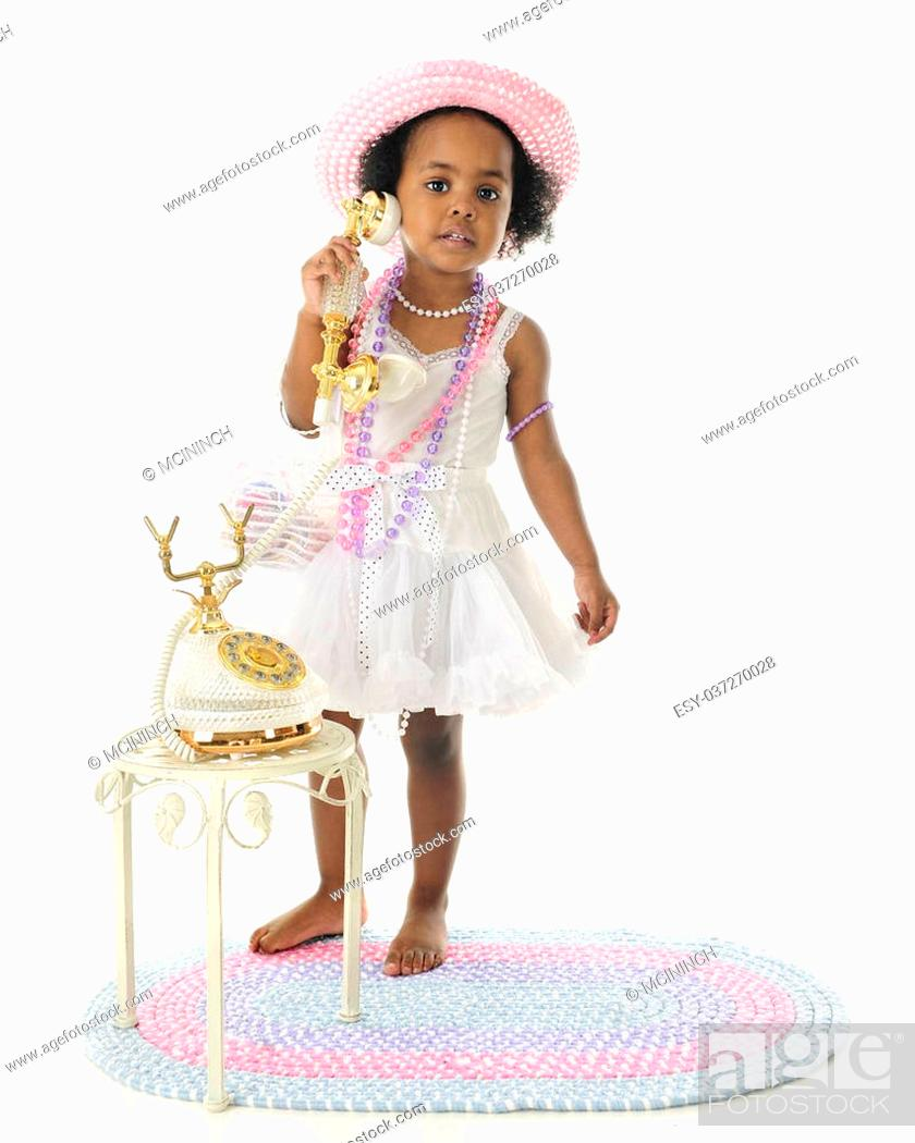 Stock Photo: An adorable 2 year old diva calling the viewer to her fancy French phone. She wears a white slip and petticoat, and pastel hat and beads.
