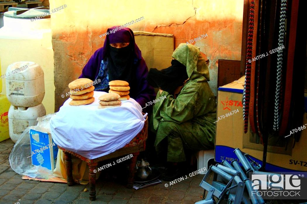 Stock Photo: Muslim with veil sells Fladenbrot in the Medina of Marrakesch (Souk).