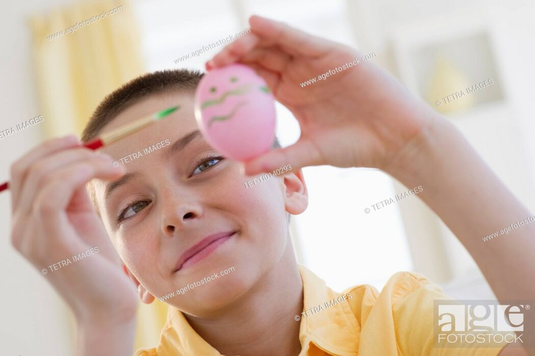 Stock Photo: Young boy decorating an Easter egg.