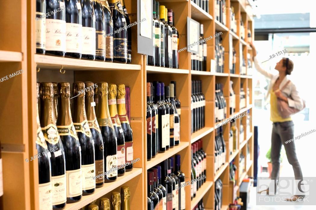Stock Photo: Woman looking at wine in shop.
