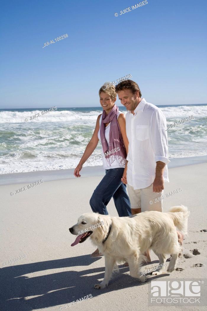 Stock Photo: Couple walking dog on beach.