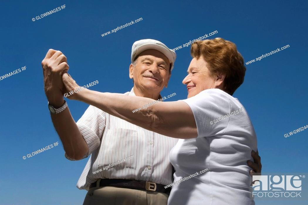 Stock Photo: Low angle view of a senior couple dancing.