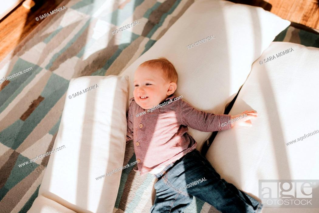 Stock Photo: Baby boy lying on cushions on living room floor, overhead view.
