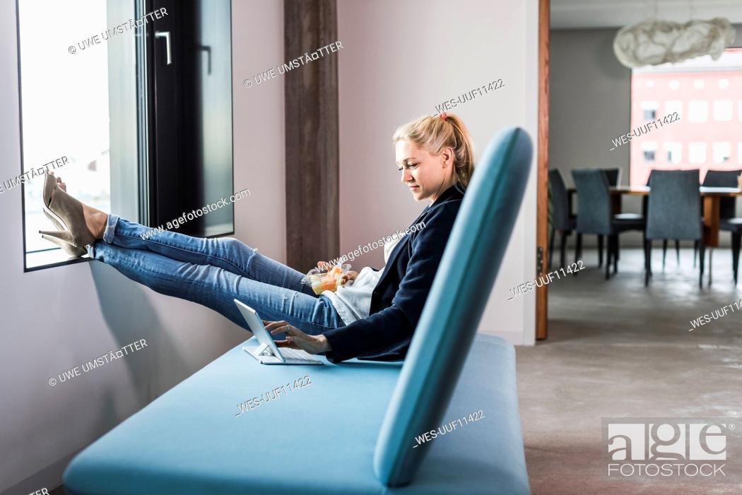 Stock Photo: Businesswoman sitting on couch with feet up using tablet.