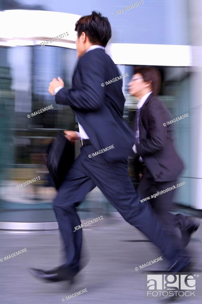 Stock Photo: Two businessmen running together.