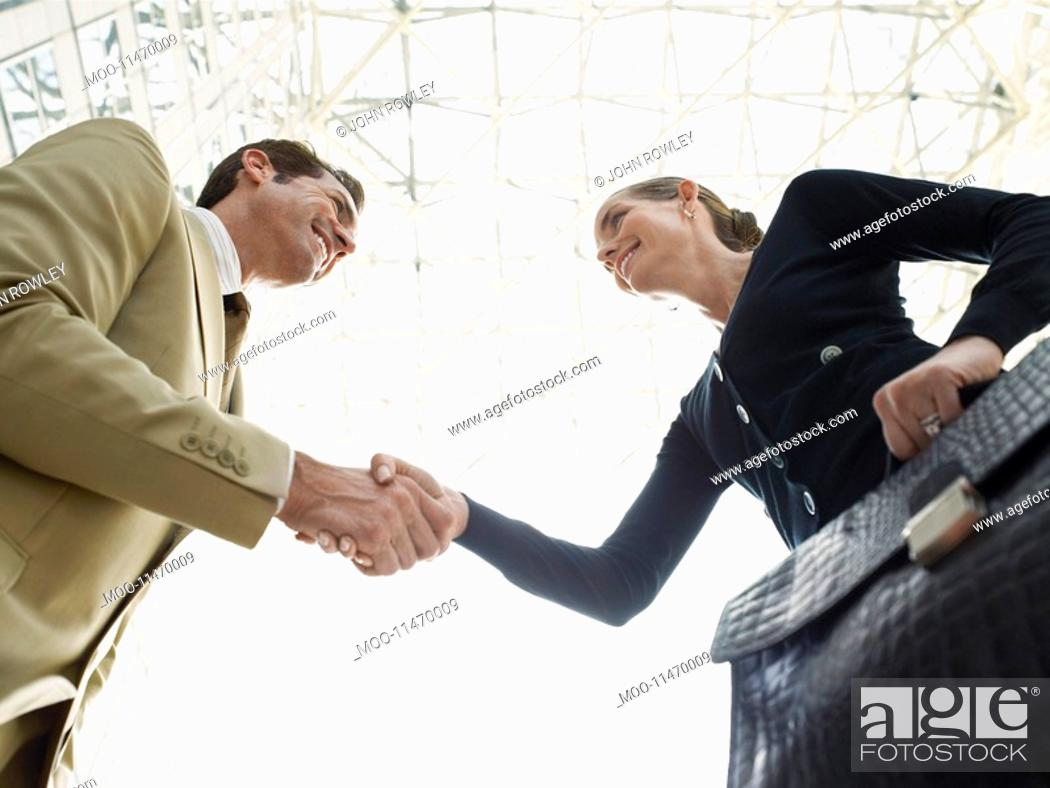 Stock Photo: Businessman and businesswoman shaking hands low angle view.