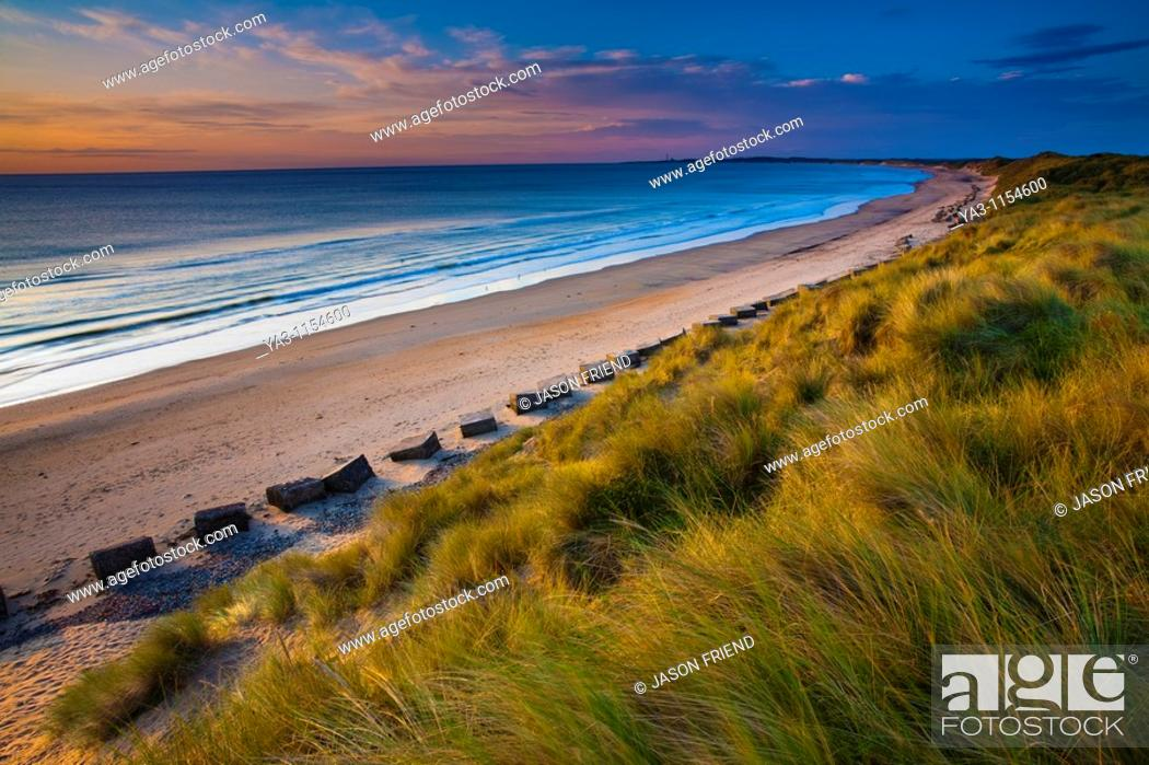 Stock Photo: England, Northumberland, Druridge Bay  A dramatic expanse of sand dunes fringing the picturesque beach at Druridge Bay, viwed shortly after sunrise.