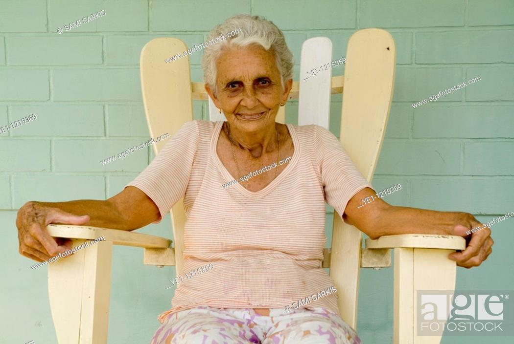 Stock Photo: Portrait of a senior Cuban woman sitting on an adirondack chair on her porch, Vinales, Pinar del Rio Province, Cuba.