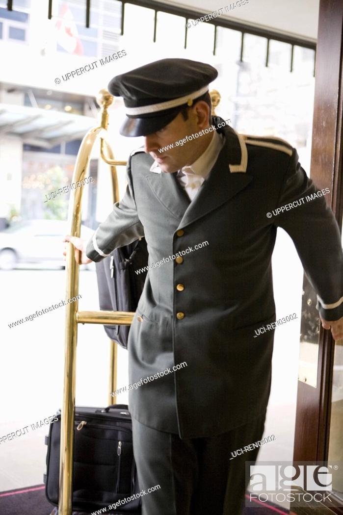 Stock Photo: Bellhop pulling luggage cart.