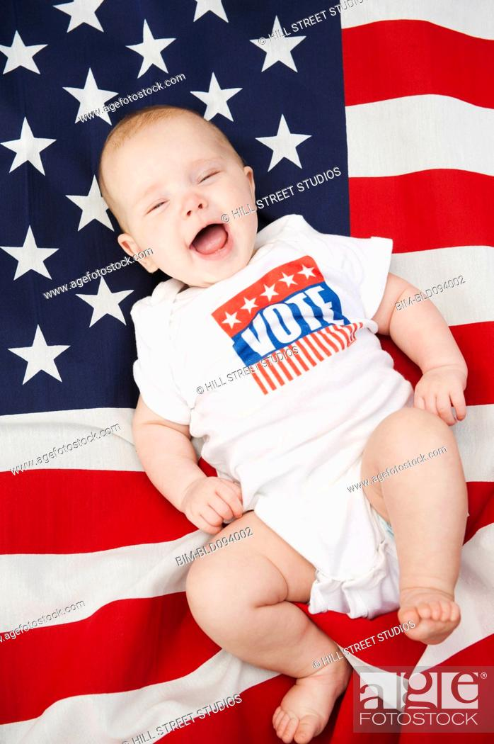 Stock Photo: Caucasian baby laying on American flag.