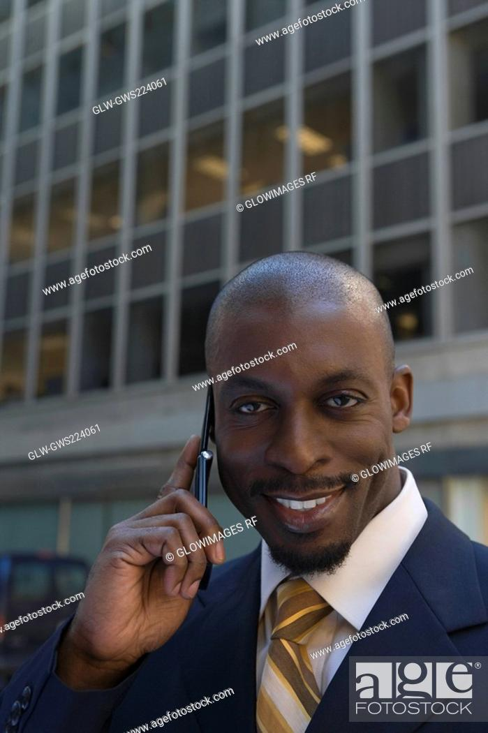 Stock Photo: Portrait of a businessman talking on a mobile phone and smiling.