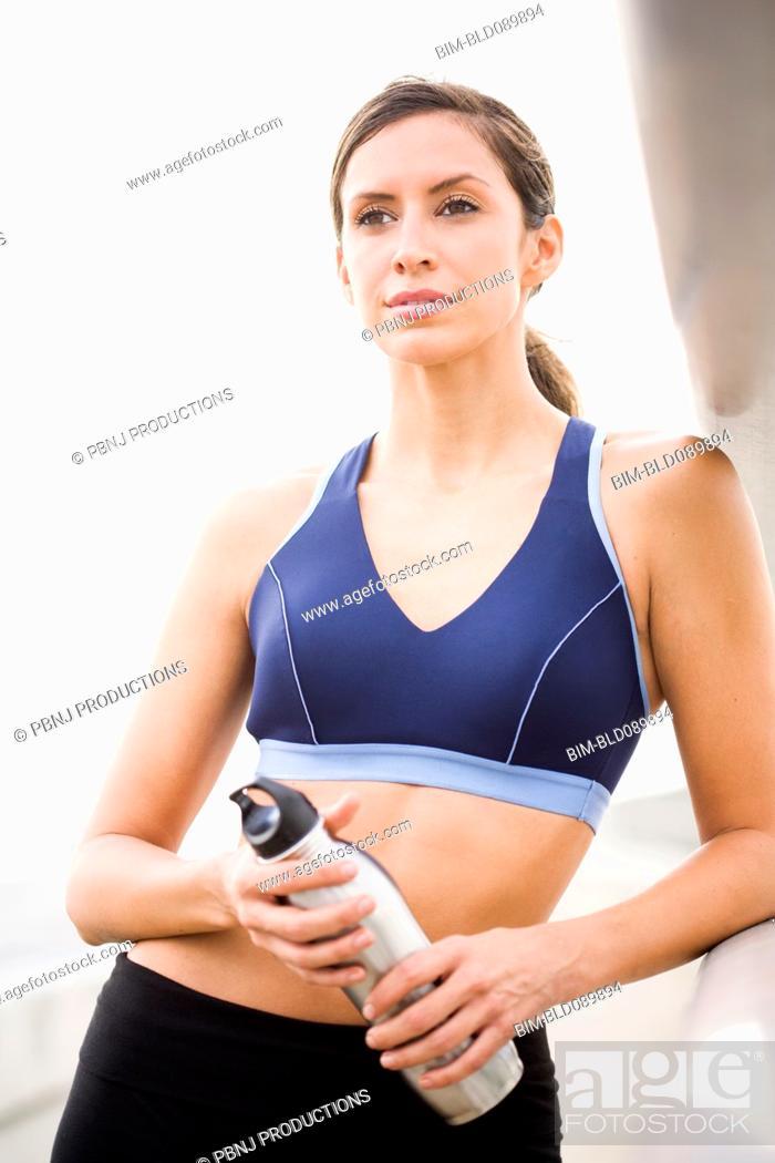 Stock Photo: Hispanic woman in sportswear holding water bottle.