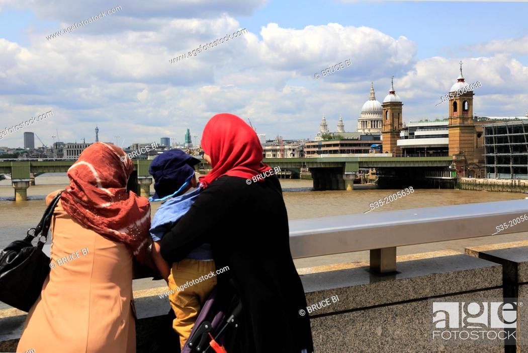 Imagen: Women with headkerchief looking at River Thames with Cannon Street Railway Bridge and the dome of St Paul's Cathedral in the background. London.