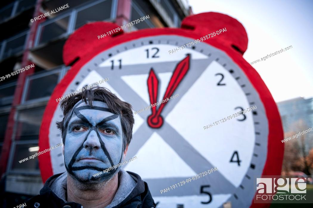 Stock Photo: 29 November 2019, North Rhine-Westphalia, Duesseldorf: A demonstrator stands in front of a clock with its hands set at five past twelve.