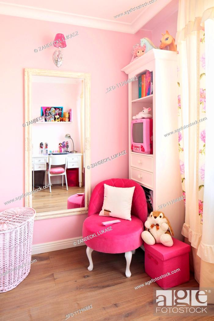 Stock Photo   White Antique Style Furniture And A Neon Pink Upholstered  Chair Against A Pale Pink Painted Wall In A Little Girlu0027s Bedroom
