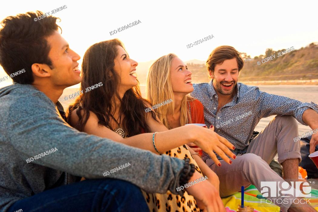 Imagen: Group of friends sitting together on beach.