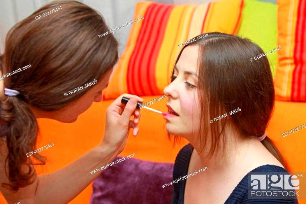 Stock Photo: A stylist putting on lip gloss on a girl's face.