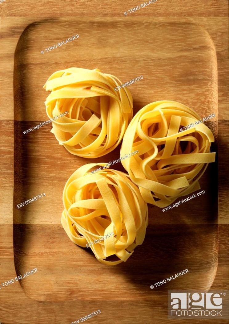 Stock Photo: Dried macro noodles yellow pasta, studio shot texture over oriental warm wood plate.
