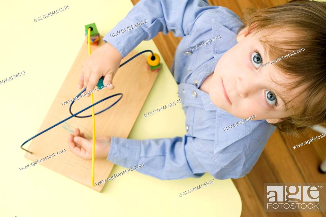 Stock Photo: Portrait of a boy playing with a toy.