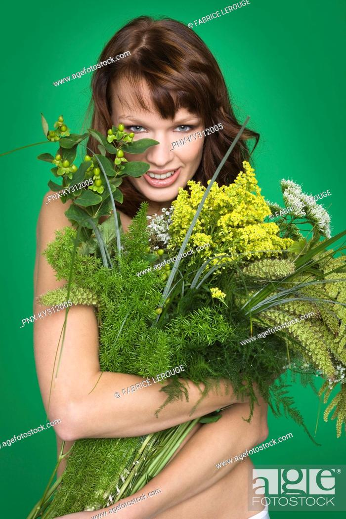 Stock Photo: Young woman covering breast with flowers.