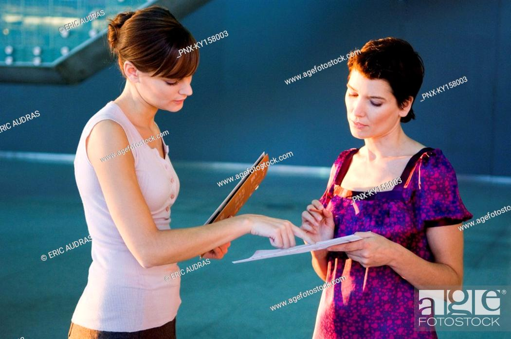 Stock Photo: Side profile of two interior designers discussion on a blueprint.