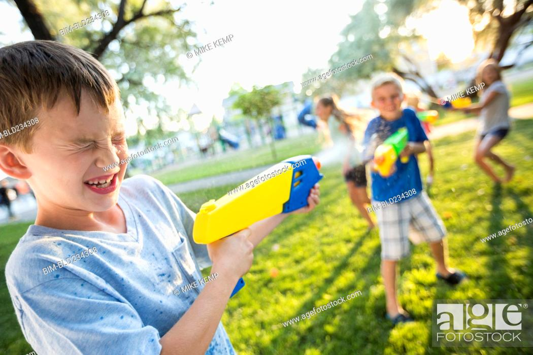 Stock Photo: Caucasian boys and girls playing with squirt guns.
