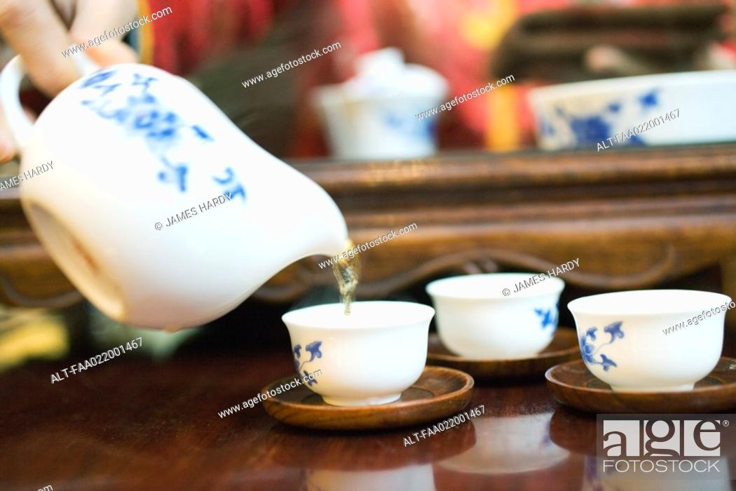 Stock Photo: Woman pouring tea, cropped view.