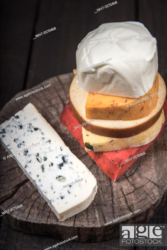 Stock Photo: many kinds of cheeses on wooden end of a tree.