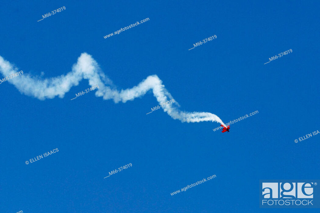 Stock Photo: Stunt plane spiraling across the deep blue sky in an air show.