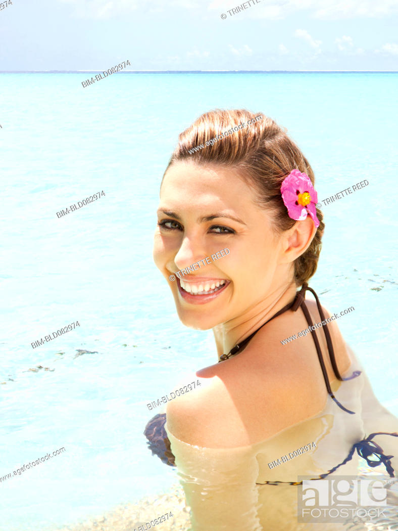 Stock Photo: Smiling Caucasian woman swimming in ocean.