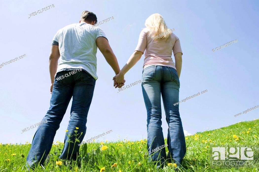 Stock Photo: Germany, Bavaria, Munich, Young couple holding hands, rear view.