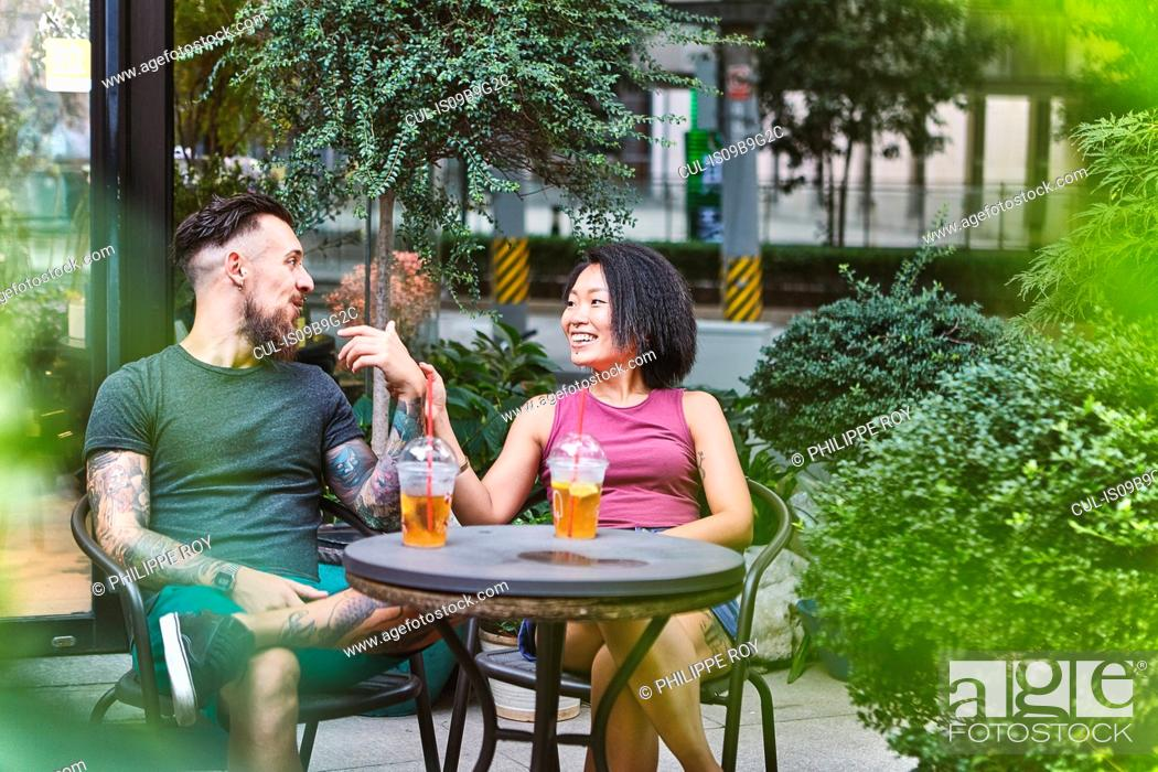 Stock Photo: Multi ethnic hipster couple talking at sidewalk cafe, Shanghai French Concession, Shanghai, China.