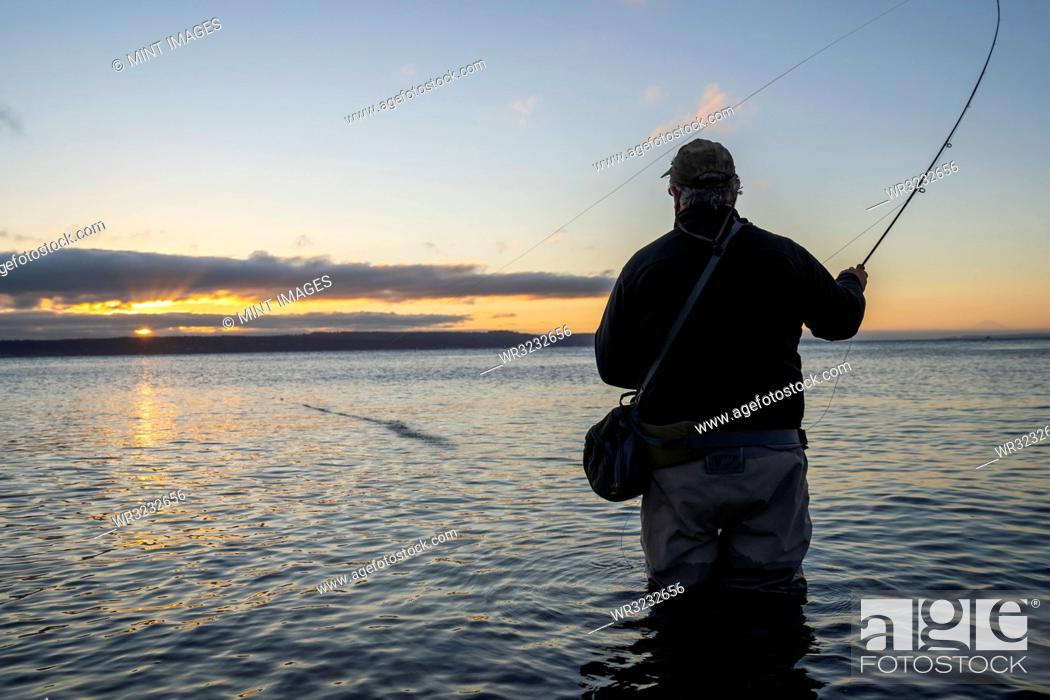 Imagen: A silhouette view of a fly fisherman casting for salmon and searun coastal cutthroat trout from a salt water beach at a beach on the north west coastline of the.