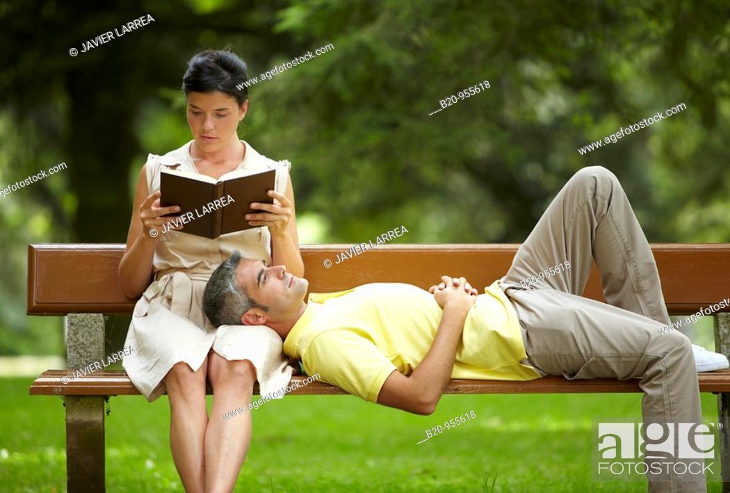 Stock Photo: Woman reading a book and man in a garden, spa-relais. Lierganes hotel and spa, Cantabria, Spain.