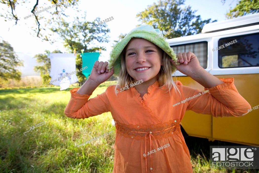 Stock Photo: Girl 9-11 holding hat on head by camper van in field, smiling, close-up.