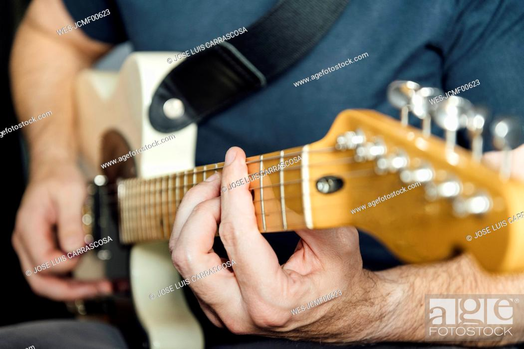 Imagen: Man learning to play electric guitar.