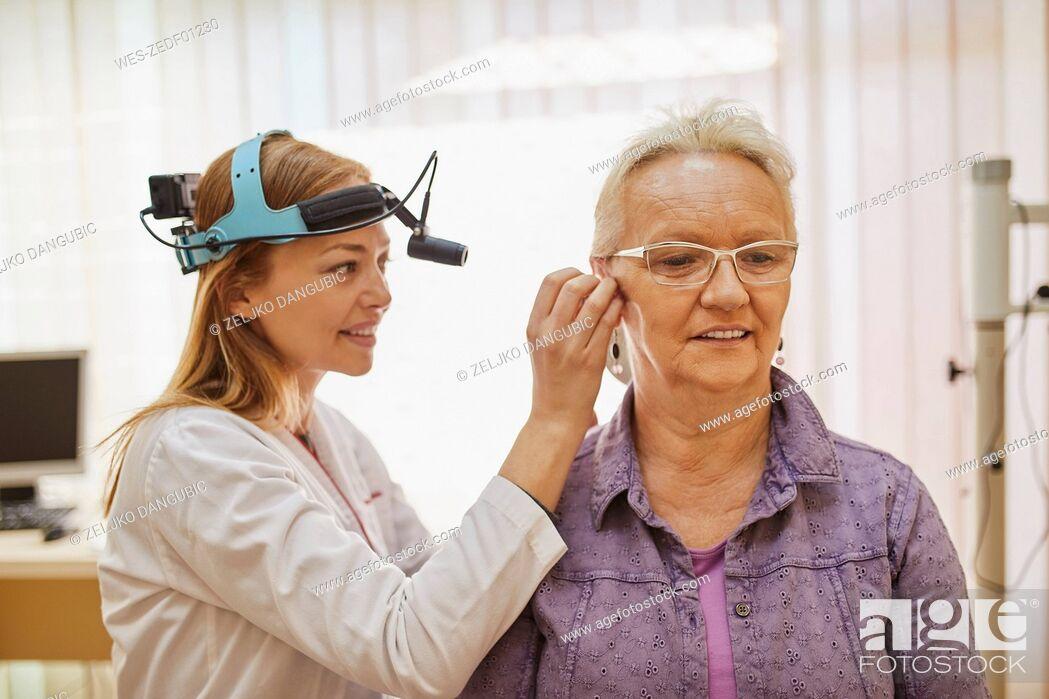 Stock Photo: ENT physician examining ear of a senior woman.