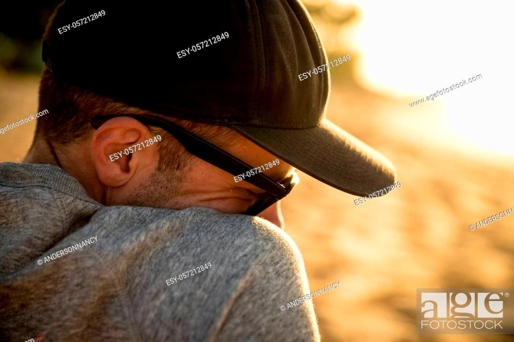 Stock Photo: Closeup head and shoulder profile of handsome male with hat and sunglasses on beach in Hawaii.