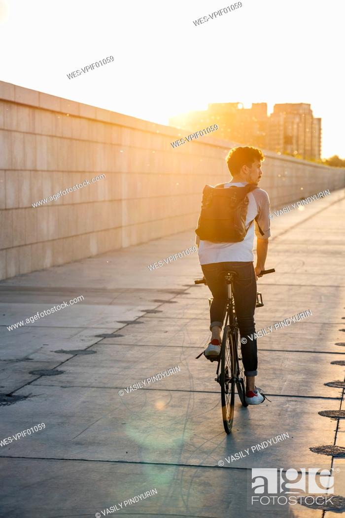Stock Photo: Young man with backpack riding bike on promenade at sunset.