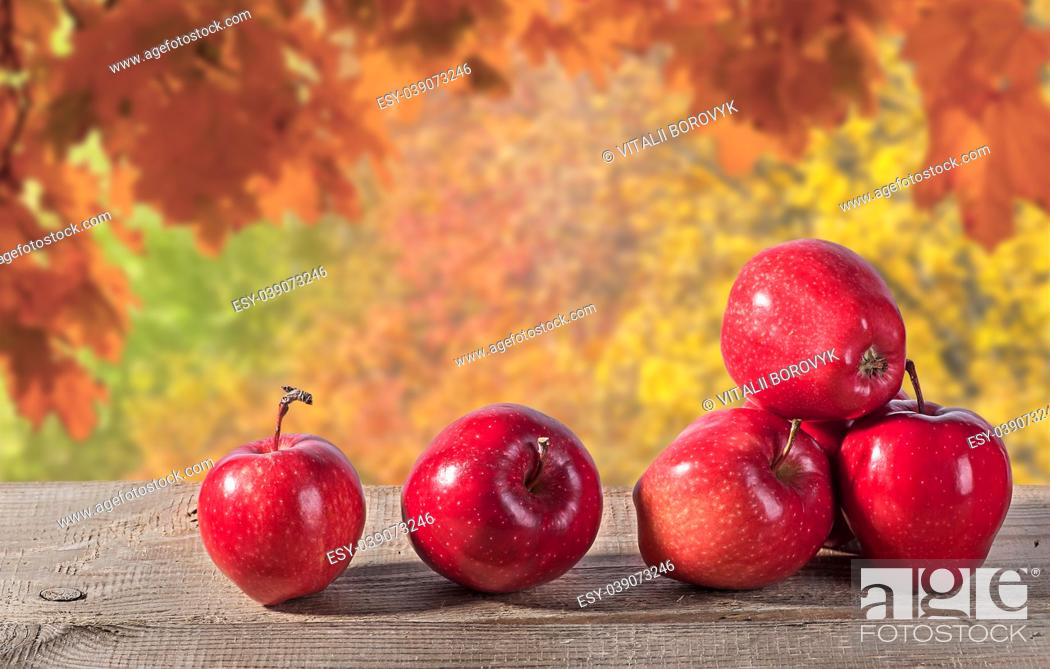 Stock Photo: Red apples on a wooden table. Autumn forest in the background. Blurred background.