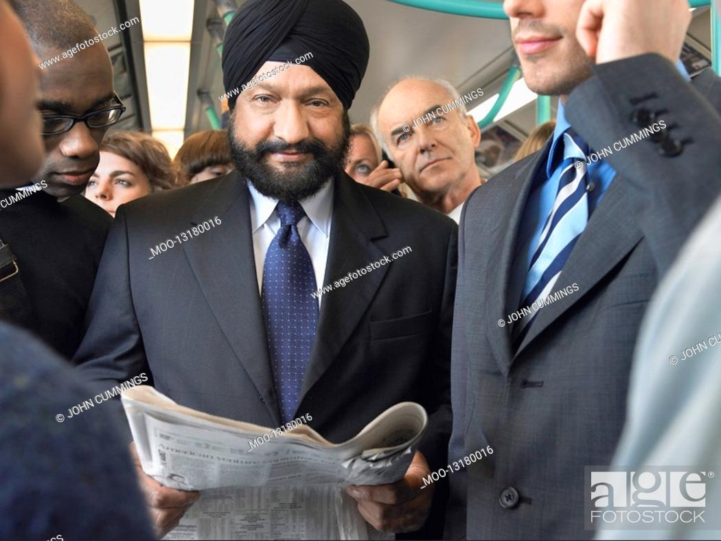 Stock Photo: Commuter in turban Reading paper on Train.